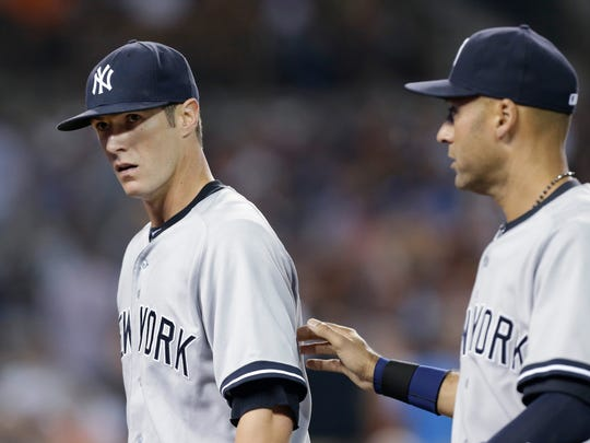 New York Yankees pitcher Shane Greene, left, is patted on the back by teammate Derek Jeter after the fourth inning of a baseball game against the Detroit Tigers in Detroit, Wednesday, Aug. 27, 2014. (AP Photo/Paul Sancya)