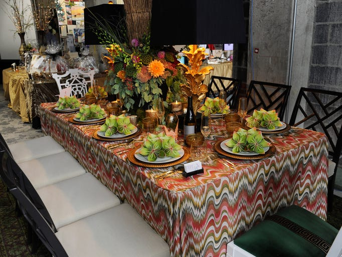 """Designer Corey Damen Jenkins of Design With Vision Elegant Interiors says his concept was """"Rooftop Paradise."""" He chose a chevron textile with autumnal color palette for the fitted table skirt. He mixed Chippendale chairswith Fretwork-styled side seating. In the center was an eight-foot tall floral tree arrangement by Affordable Flowers."""