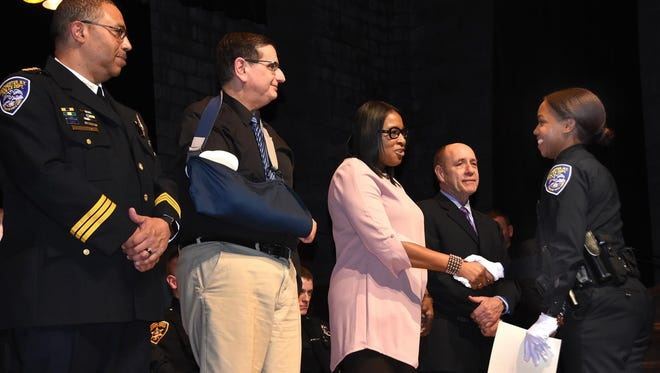 Mayor Lovely Warren, center, shakes the hand of a Rochester Police Department recruit graduate Friday.