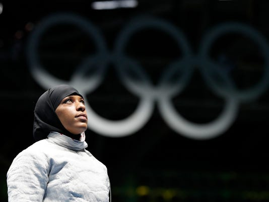 FILE- In this Aug. 8, 2016, file photo, Ibtihaj Muhammad, from United States, waits for match against Olena Kravatska from Ukraine, in the women's saber individual fencing event at the Summer Olympics in Rio de Janeiro. Members of basketball's international governing body are expected to vote to eliminate a rule that bans religious headgear during competition. The vote could come during a meeting on Thursday or Friday, May 5, 2017. Headgear was banned for safety reasons two decades ago out of fear it could fall off, causing a player to slip or become entangled. (AP Photo/Vincent Thian, File)