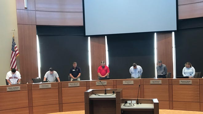 Melissa City Council members bow their heads during the invocation at the June 9 meeting.