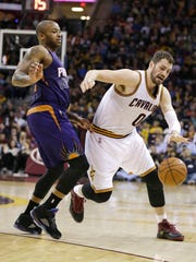 Cleveland Cavaliers' Kevin Love, right, drives past