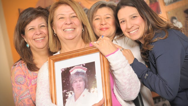 01/27/2016: Christina Calderon, second from left, holds a portrait of her late mother and NMSU nursing alumna Margaret Pacheco near the Nursing Wall of Excellence inside the NMSU College of Health and Social Services (CHSS) building. Calderon is joined by her sisters Martha Rivera, left, and Estela Heredia, second from right. Pacheco's grandaughter, Amy Lopez, appears at right. All four women are NMSU alumni, and Calderon, Rivera and Lopez are all nurses.