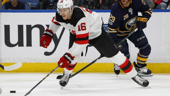 New Jersey Devils defenseman Steve Santini (16) controls the puck during the first period of an NHL hockey game against the Buffalo Sabres, Monday Oct. 9, 2017, in Buffalo, N.Y.