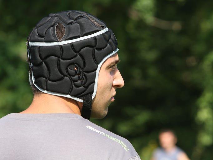Joe Fromer, a goalie on the Byram Hills boys soccer team, wears a protective helmet as he practices with the team, Aug. 20, 2014.  Head coach Matty Allen is requiring his goalies to wear the protective helms this season.