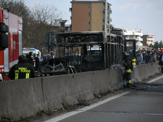 Firefighters stand by the gutted remains of a bus in