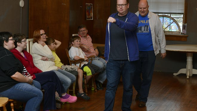Members of the audience watch as Micahel Brinson and Mike Brustad of First City Improv act out the day of one of the audience members Sunday during Shenanigans, an audeince participation improvisational theater in Old Sacred Heart on 12th Ave.