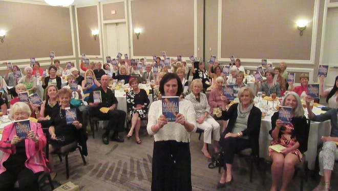 """Author Marcia Clark and guests at her Author Luncheon event display her latest book, """"Moral Defense."""""""