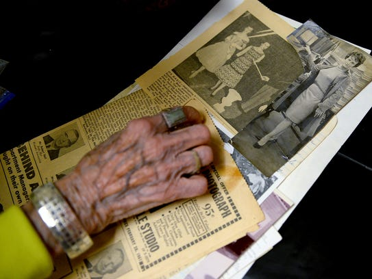 Betty Collette, 91, flips through newspaper clippings
