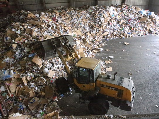 A front-end loader piles newly arrived recyclable materials