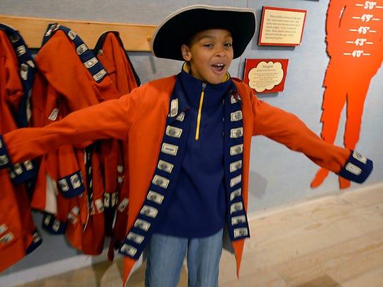 Delton-Kellogg fourth grader Jayden Higden tries on a British Colonial soldier's uniform.