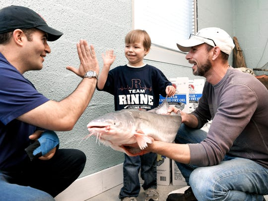 Caleb Daniel, 5, of Franklin high-fives Preds catfish thrower Tom Dennis, while Little's Fish Market owner Chris Little show Daniel the catfish he will help throw on to the ice before Preds game on Saturday. While Daniel lived at Vanderbilt Children's waiting for a heart transplant, he would throw his stuffed catfish off the bed.