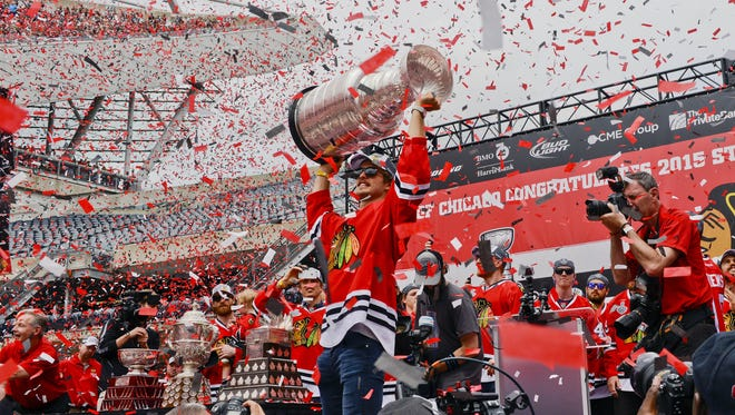 Chicago Blackhawks defenseman Niklas Hjalmarsson holds the Stanley Cup Trophy up during the team's celebration rally.