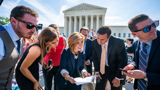 Kristen K. Waggoner (C), a senior vice president with the conservative Christian organization Alliance Defending Freedom (ADF), reads the Supreme Court ruling on a California abortion issue outside the Supreme Court.