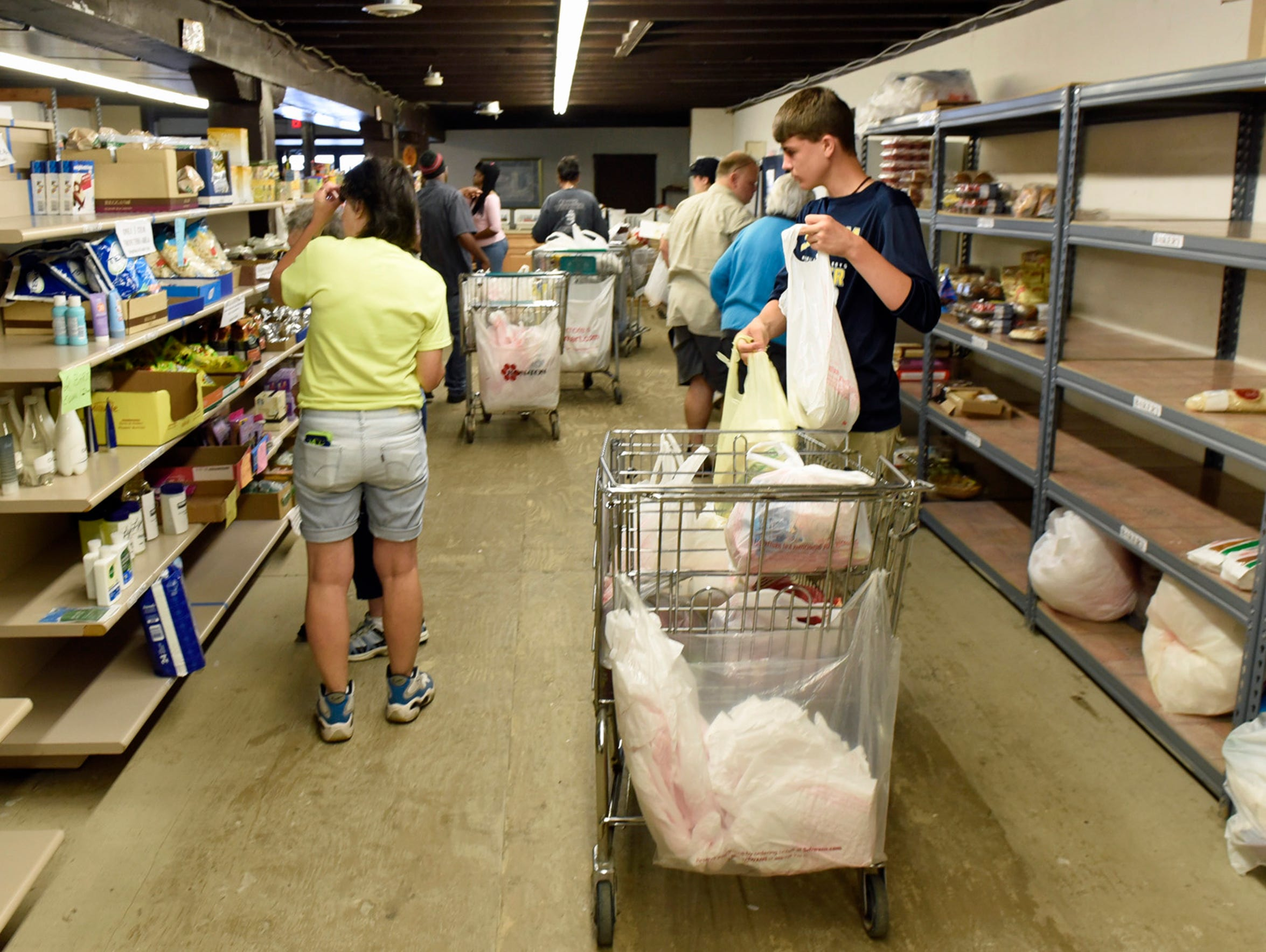 Volunteers and patrons pick up groceries Thursday,