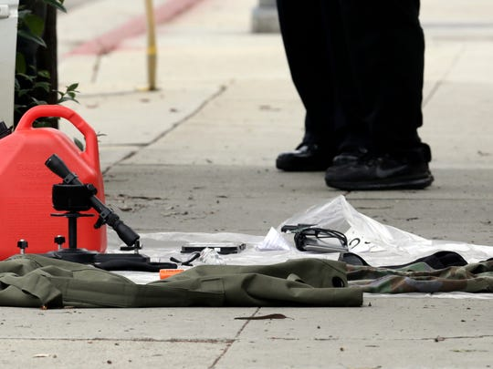 Items removed from a car are displayed on a sidewalk after a heavily armed man was arrested in Santa Monica, Calif., early Sunday, June 12, 2016.