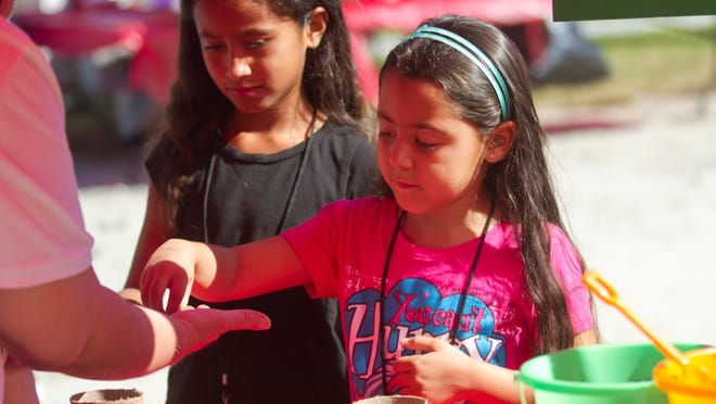 Ariana Gomez, 7, and Kalani Reyes, 6, right, plant vegetable seeds to grow at home at Kids in the Kitchen. The event, sponsored by the Junior League, taught children how to stay healthy and active.