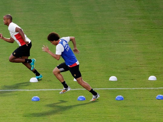 Belgium captain Vincent Kompany, left, who is recovering from an injury, and Axel Witsel take part in a training session at Estadio Manoel Barradas, the day before the World Cup round of 16 soccer match between Belgium and USA at Arena Fonte Nova in Salvador, Brazil, Monday, June 30, 2014. (AP Photo/Julio Cortez)