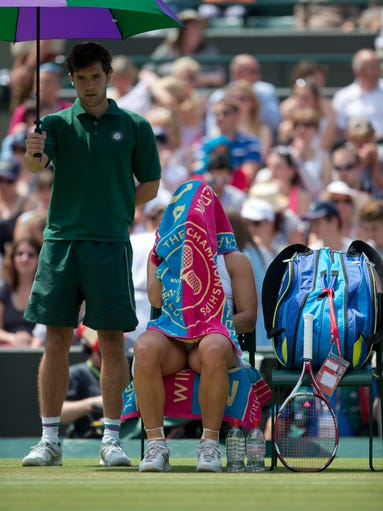 Jul 2, 2014; London, United Kingdom; Angelique Kerber (GER) under her towel on a change of ends  during her match against Eugenie Bouchard (CAN) on day nine of the 2014 Wimbledon Championships at the All England Lawn and Tennis Club. Mandatory Credit: Susan Mullane-USA TODAY Sports ORG XMIT: USATSI-178712 ORIG FILE ID:  20140702_jla_au2_017.jpg