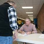 Election officials; Tom Aldred, left, and Melissa Daniels check a voter in at the Eastern High School voting precinct. 'I've seen more voters in their 50's or older voting, but more younger people overall at the election this time around,' Daniels said. Nov., 4, 2014