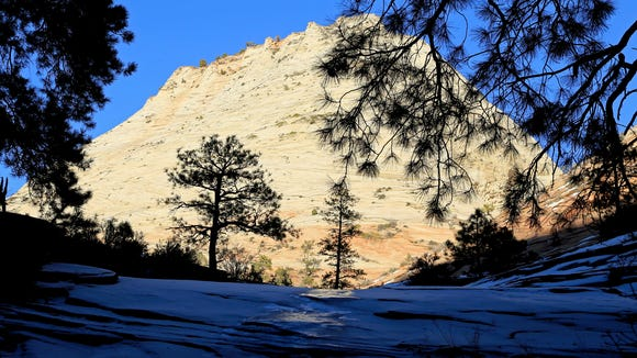 Snow and ice contrast with sandstone cliffs bathed in sunlight on the east side of Zion National Park.