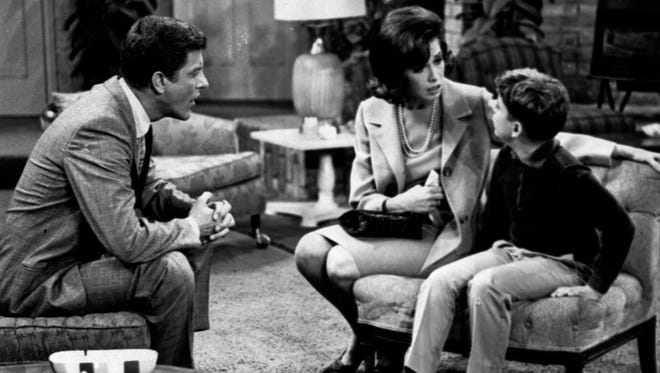 In this 1965 file photo, from left, Dick Van Dyke, as Rob Petrie, and Mary Tyler Moore, as Laura Petrie, talk to Larry Matthews, who plays their son, Ritchie, on The Dick Van Dyke Show.