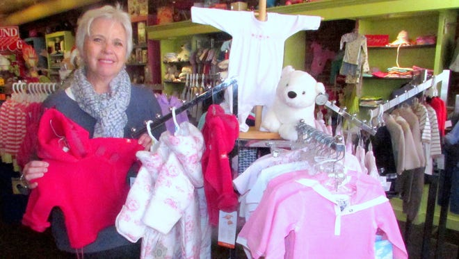 Owner Ginny Coon shows off some of the children's items for sale at Imagine That! on Market Street in Corning.