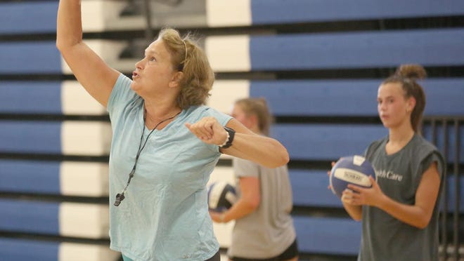 "Boonville Lady Pirates volleyball coach Dina Herzog goes over a serving drill during camp Monday at the Windsor gymnasium. Herzog said 33 girls in grades 9-12 participated in the first day of practice on Monday. ""We will work on fundamentals and conditioning early this week and then will transition to team play later in the week,"" Herzog said. ""We've got great numbers and the girls are working hard knowing how competitive it is this year. Each girl will be given a chance to showcase their talents."""