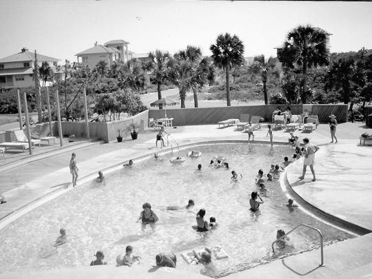 People swim in the pool in this undated black and white