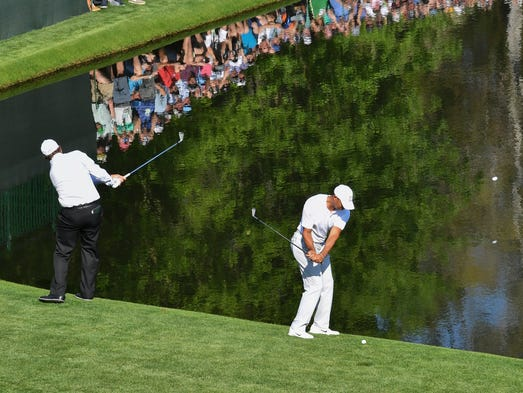 Phil Mickelson (left) and Tiger Woods skip their balls