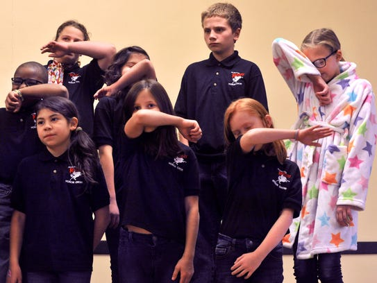 """Members of the Austin Elementary School Choir pantomime wiping their faces on their sleeves while performing a song called, """"I've got a cold in my nose."""" Their program was sung in the Elks Art Center Ballroom as part of the lead-up to the City Sidewalks Christmas Parade Tuesday."""