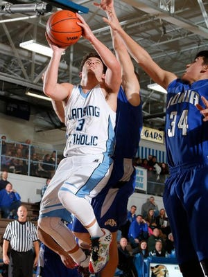 Ionia's Kollin Leonard, left, and Lansing Catholic's Jack Peters battle for the ball Friday, Jan. 9, 2015, in Lansing, Mich.