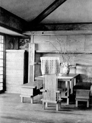 Dining room and dining Room table at Taliesin.  The built-in set of drawers and cabinets line the back wall of the room.  A drawing, possibly a Japanese print, hangs above the drawers. WHS Image ID 29072.
