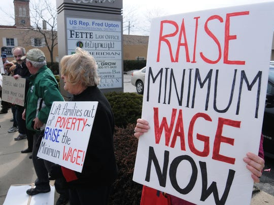People call for an increase in the minimum wage outside the district office of Rep. Fred Upton, a Michigan Republican, in 2014.