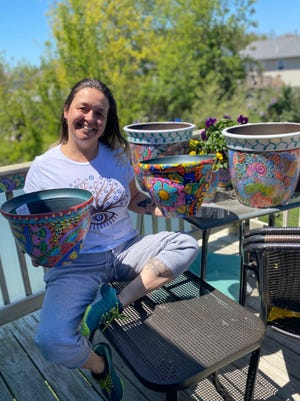 Gabriela Roias, at her home in Fall River, is surrounded by some of the flower pots she adorned.
