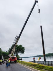 A Landwehr Construction crane lifts an anchor post into position above the fireworks barge during assembly Tuesday along the banks of the Mississippi River in St. Cloud.