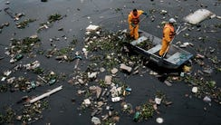 Workers gather debris carried by the tide and caught