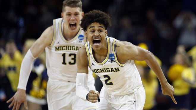 Michigan guard Jordan Poole (2) is chased by forward Moritz Wagner (13) after making a 3-point basket at the buzzer to win an NCAA men's college basketball tournament second-round game against Houston on Saturday, March 17, 2018, in Wichita, Kan. Michigan won 64-63.