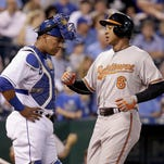Baltimore Orioles' Jonathan Schoop (6) runs past Kansas City Royals catcher Salvador Perez to score after hitting a two-run home run during the fourth inning Wednesday in Kansas City.