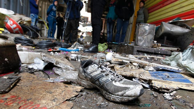 Iraqis look at the aftermath following a double blast in a busy market area in Baghdad's central al-Sinek neighborhood on Dec. 31. Baghdad has been on high alert since the Oct. 17 offensive to retake Mosul.
