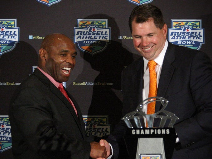 Louisville head coach Charlie Strong, left, and Miami head coach Al Golden greet in front of the Russell Athletic Bowl trophy in Orlando, Fla., Dec. 27, 2013 the day before their teams face off in the Russell Athletic Bowl.