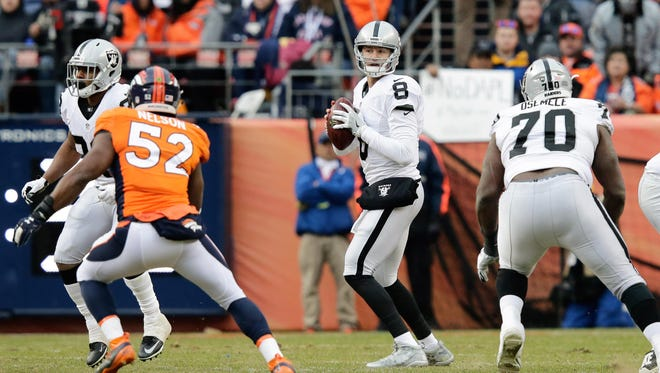 Oakland quarterback Connor Cook (8) drops back to pass against Denver in Sunday's second quarter.