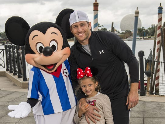"""LAKE BUENA VISTA, FL - DECEMBER 29: In this handout photo provided by Disney Parks, the new bachelor on ABC's """"The Bachelor"""" and former professional soccer player, Juan Pablo Galavis poses with Mickey Mouse and his daughter, Camila Valentina Galavis at the Epcot Theme Park at Walt Disney World Resort on December 29, 2013 in Lake Buena Vista, Florida. The 18th season of """"The Bachelor"""" begins on January 5, 2014. (Photo by Matt Stroshane/Disney Parks via Getty Images)"""