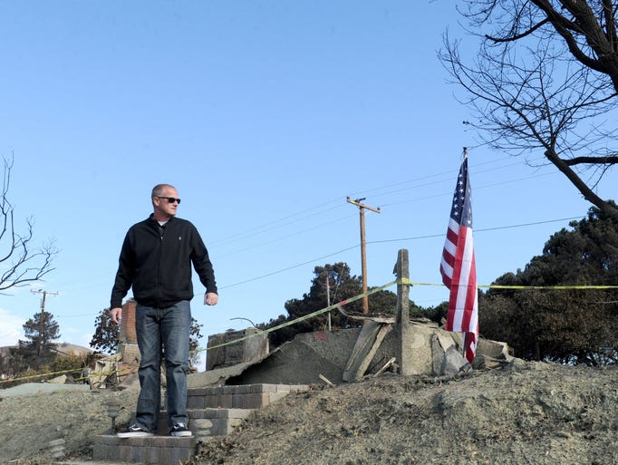 Charles Bates stands on the stairs to his Ventura house