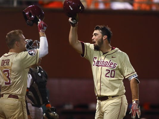 Florida State's Kyle Cavanaugh, right, taps helmets with Nick Derr after hitting a home run in the eighth inning of the team's NCAA college baseball tournament super regionalgame against Sam Houston State on Sunday, June 11, 2017 in Tallahassee, Fla. Florida State won 19-0, and advances to the College World Series. (AP Photo/Phil Sears)