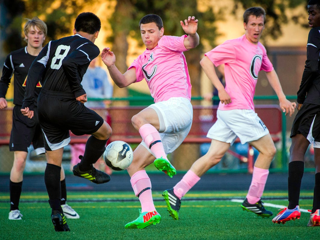 Centennial's Hunter Pinegar (pink, front) fights for a ball against Ankeny in 2014. The sophomore has scored eight goals for the unbeaten Jaguars in 2015.