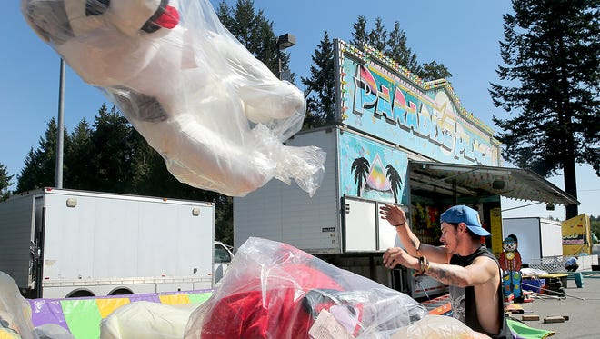 John Caudle, of Davis Amusement Cascadia, tosses a stuffed animal prize as the games area was set up Tuesday at the Kitsap County Fairgrounds. The annual Kitsap County Fair runs Wednesday through Sunday.