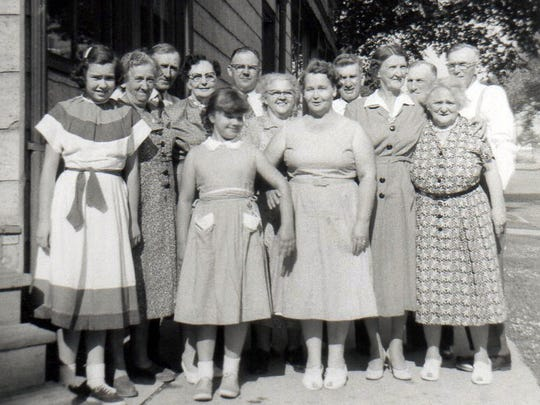 Rose Mary Zimmermann Muller (front, far left) poses with family in 1957, including her sister, Sarah Zimmermann Howard (center front), their mother Fay Zimmermann (next to Sarah), her aunt Rose Zimmermann Boguslowski (behind Fay, dress with white collar) and father, George Zimmermann (peering between Fay and Rose).