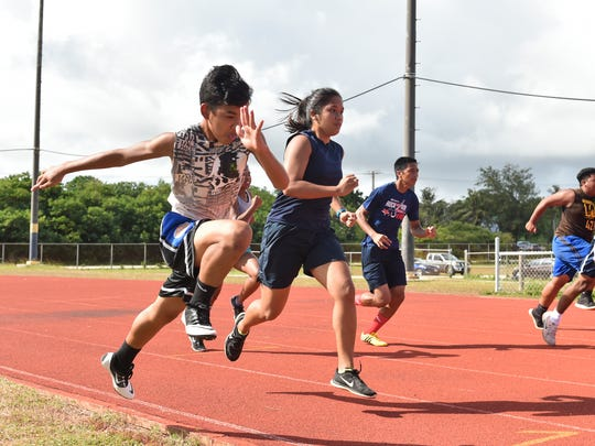 Members of the George Washington High School track and field team work on drills at the GW track in Mangilao on May 17, 2017.