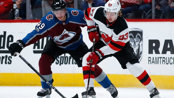 Colorado Avalanche defenseman Samuel Girard, left, steals the puck from New Jersey Devils left wing Jesper Bratt in the first period of an NHL hockey game Friday, Dec. 1, 2017, in Denver. (AP Photo/David Zalubowski)